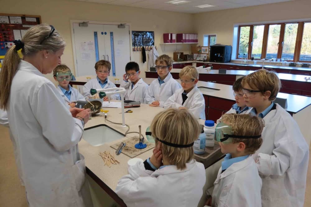 Science lab teacher and boys white lab coats Elstree School Woolhampton Berkshire