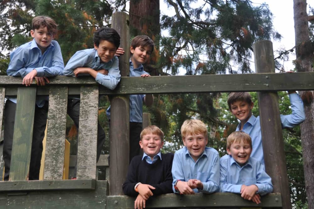 Elstree School Woolhampton Berkshire boys blue shirts grey trousers on wooden adventure playground
