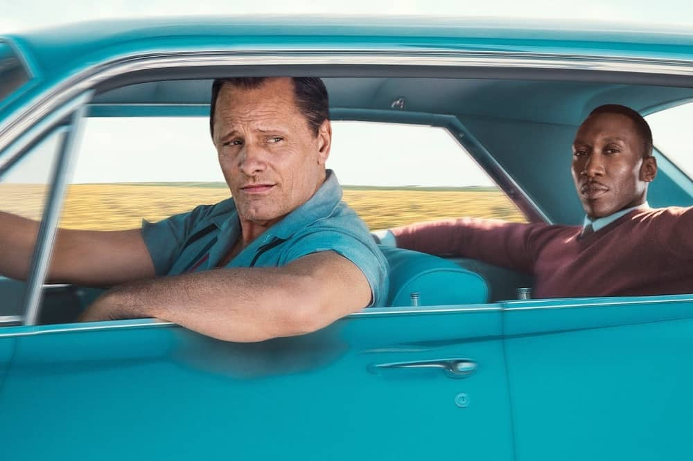 Green book turquoise car white man driving black man sat on backseat