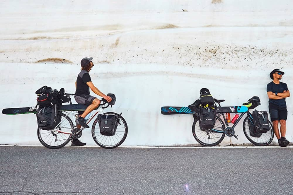 Banff Mountain Film Festival Ice & Palm two cyclists loaded with skis leaning again a stone wall