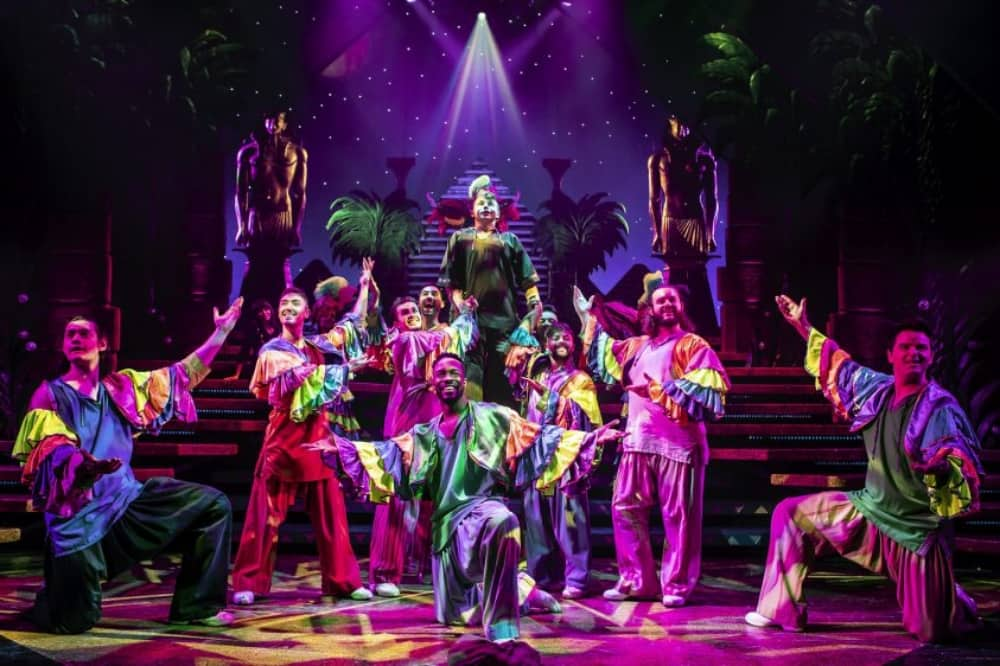 Jospeh and his technicolor dreamcoat musical 11 brothers in frilly shirt singing calypso