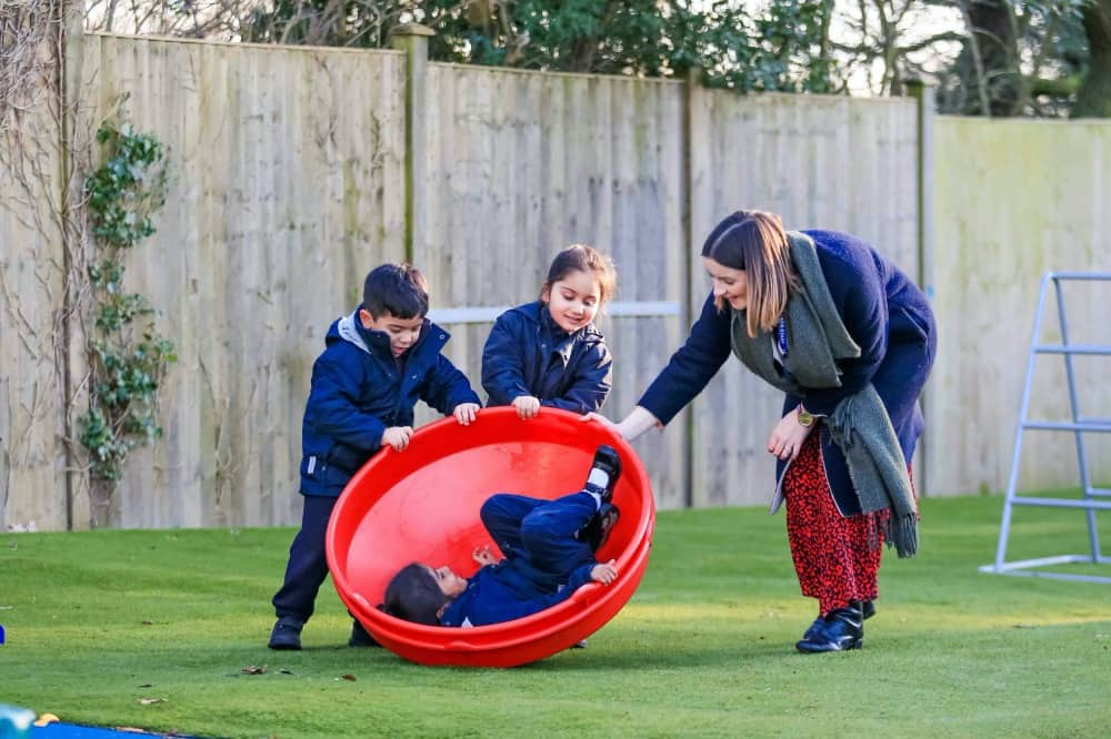 Long Close School Junior school children plat outside in red spinny toy