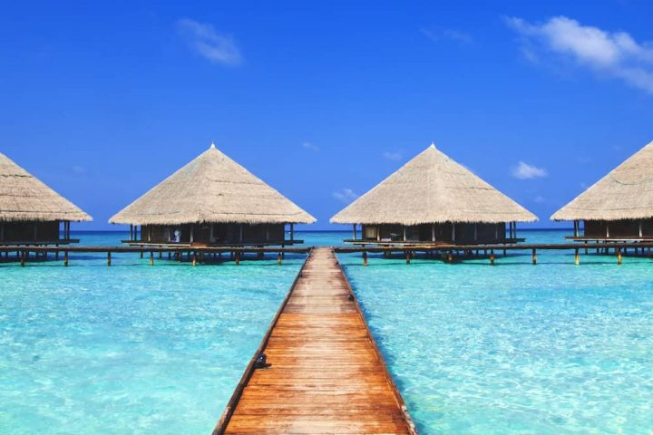 Sea villas turquoise water blue sky and wooden jetty