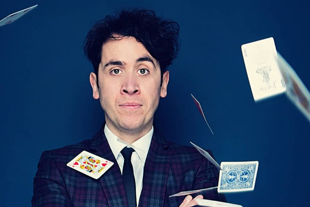 magician pete firman blue suit throwing playing cards