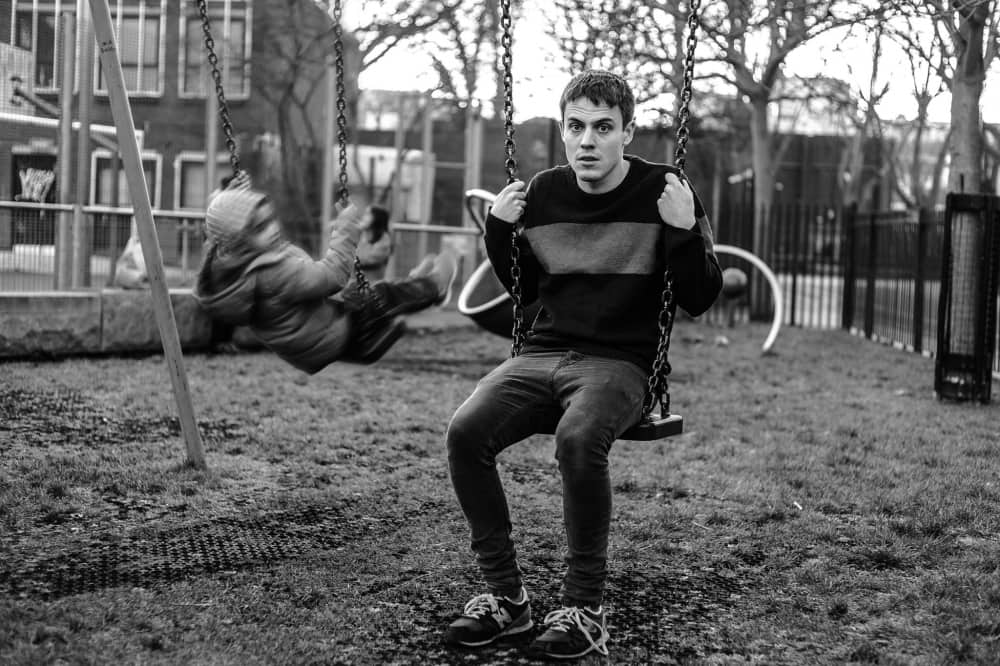 Comedian Ross Smith on kids swing in park