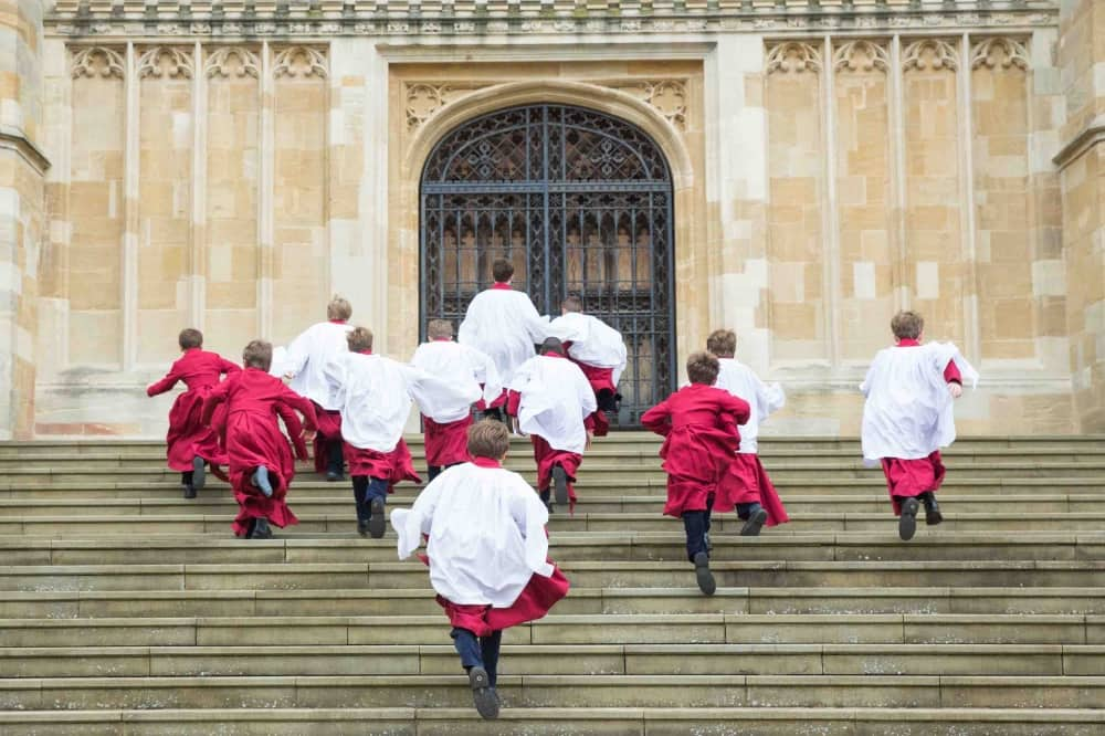 St George's Windsor choristers red and white gowns running up chapel steps