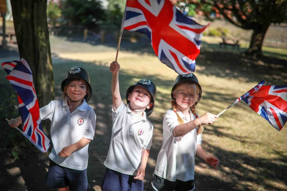 St George's Windsor Kindergarten and pre-prep children wearing policeman's helmet waving union jacks