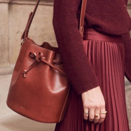 Sezane model burgundy skirt top and leather bucket bag