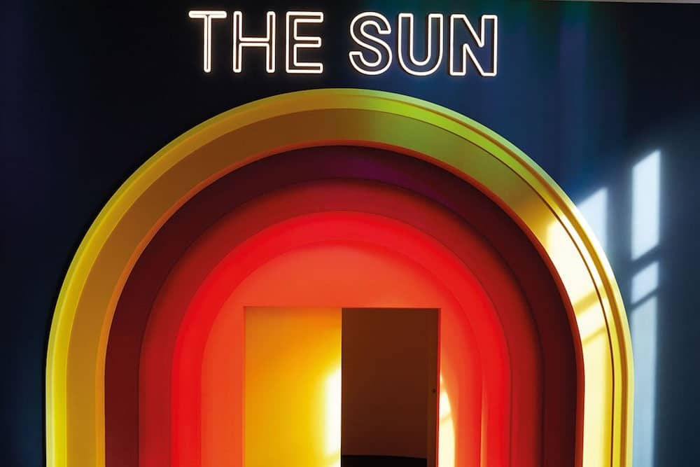 Neon sun sign and red arches around door science museum exhibition london