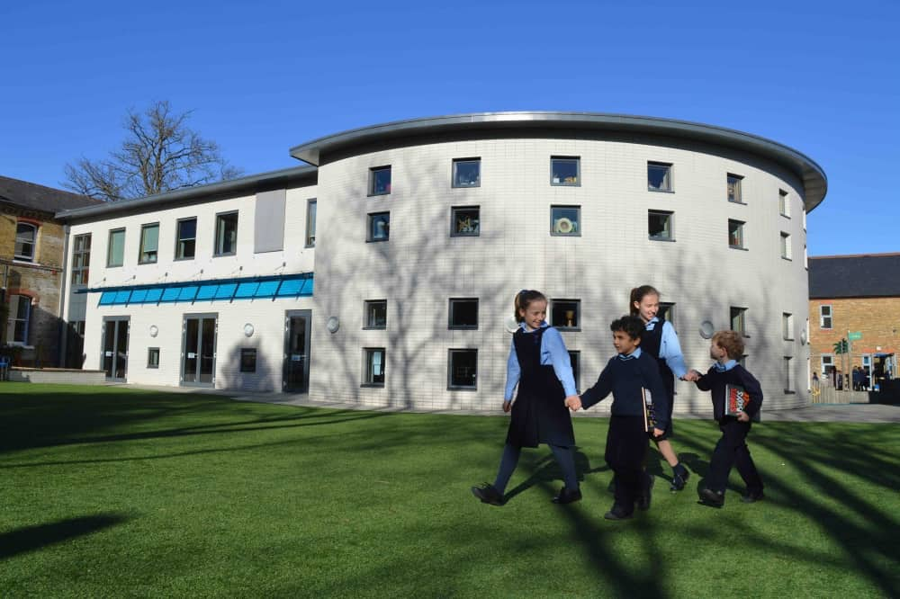Upton House School Windsor white curvy new building with kids running across the grass
