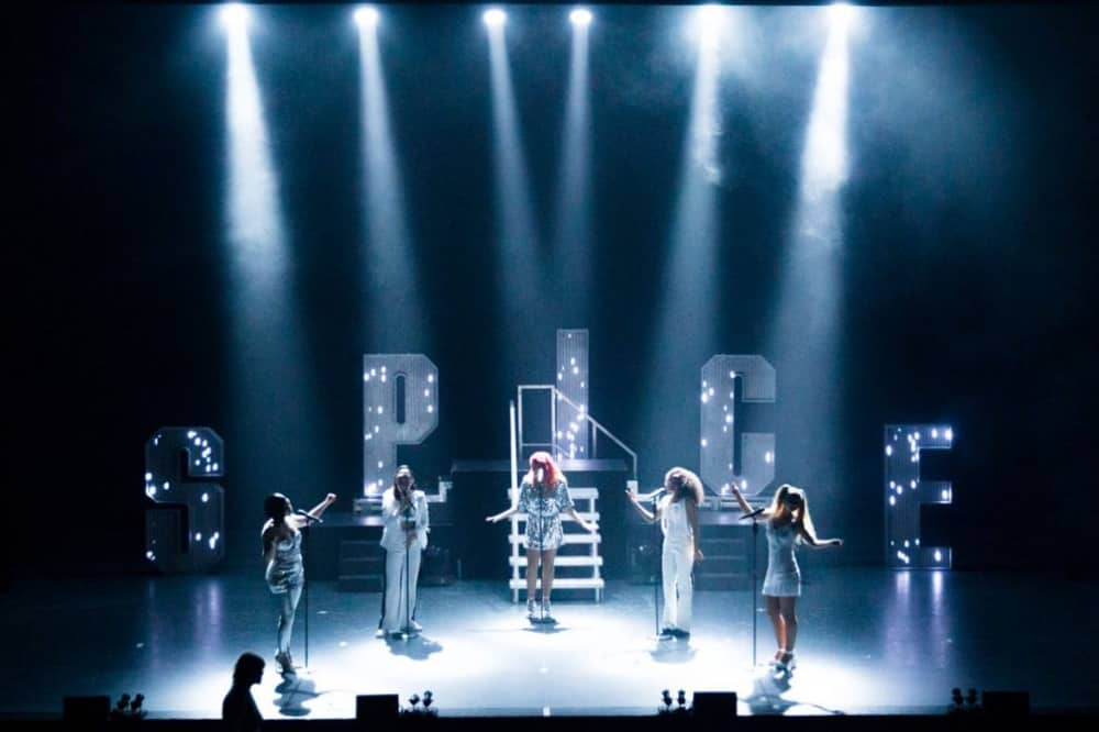 wannabe spice girls show 5 girls in spotlights in front of giant letters