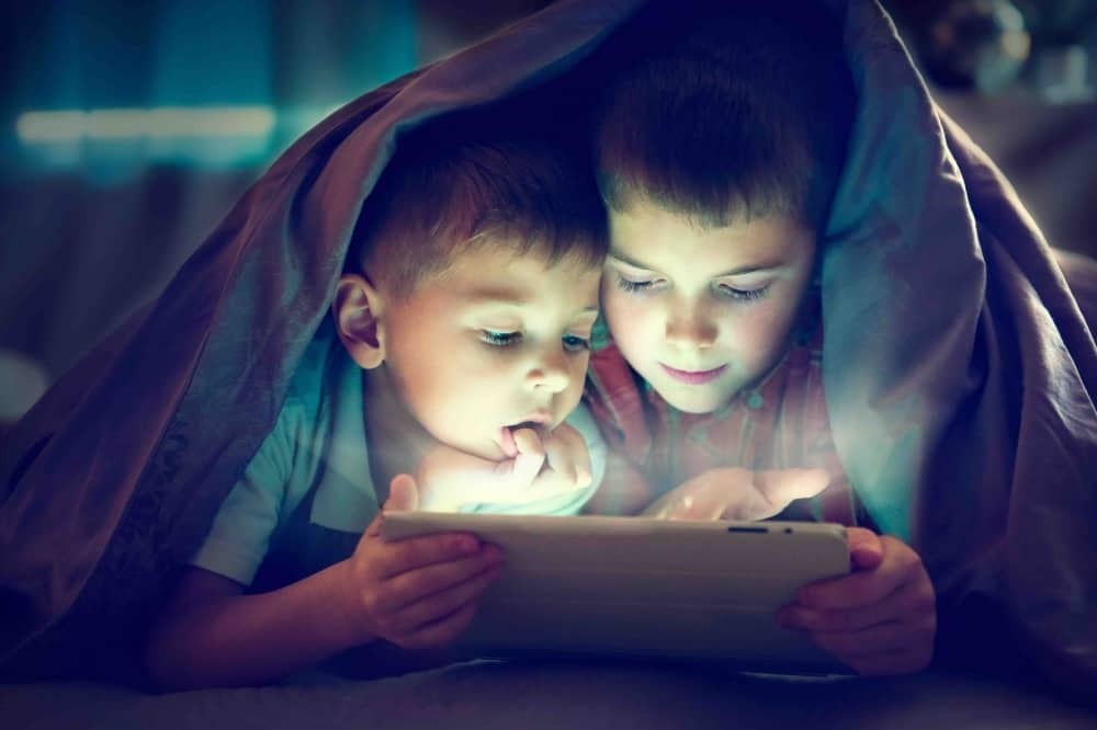 two boys under blanket looking at an iPad
