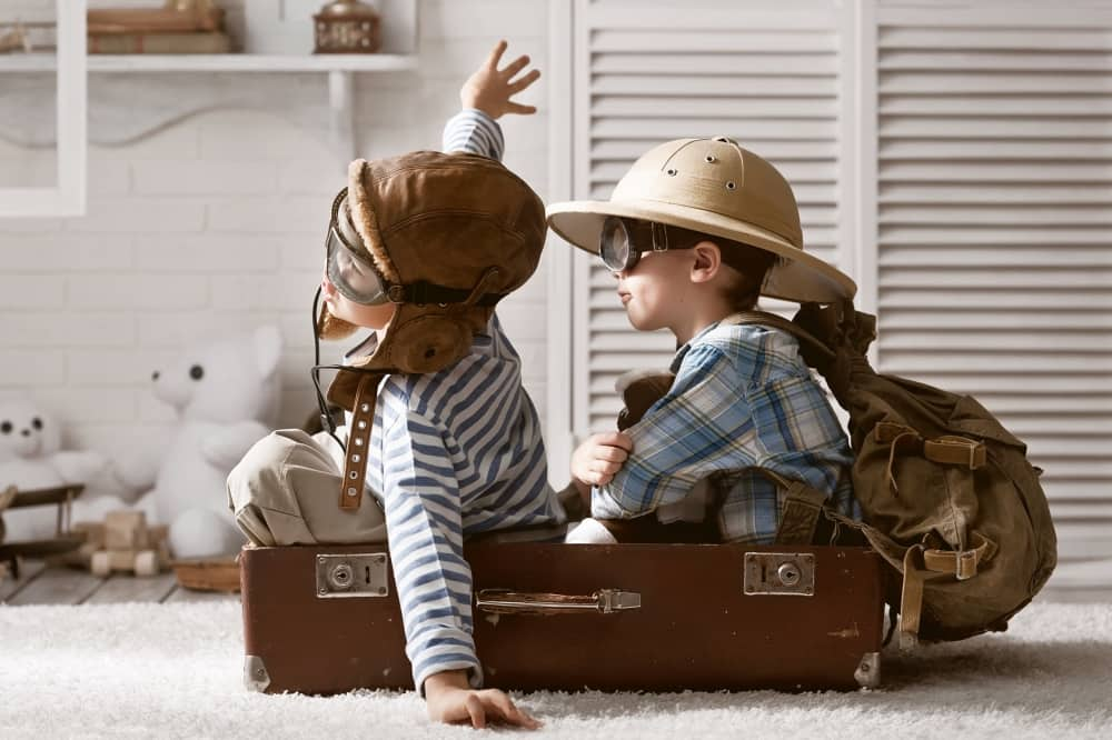 children playing make believe suitcase hats flying a plane