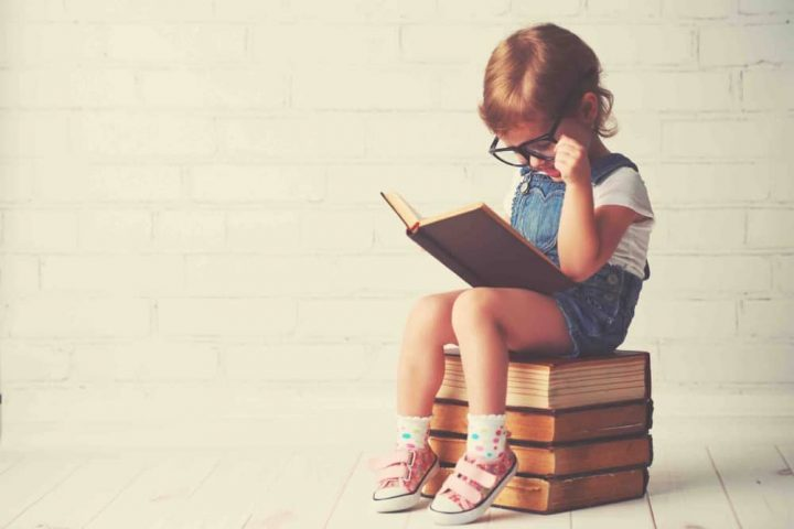 girl wearing glasses reading on pile of books