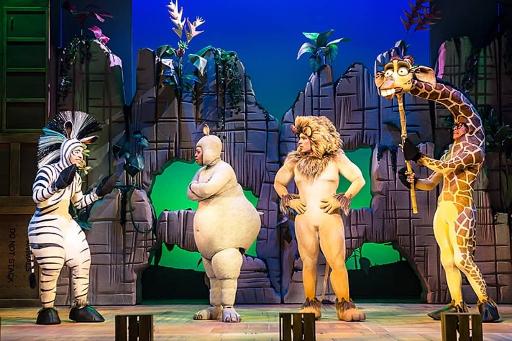 Madagascar The Musical Hexagon reading Lion Hippo, puppet giraffe and zebra on stage surrounded by tropical trees