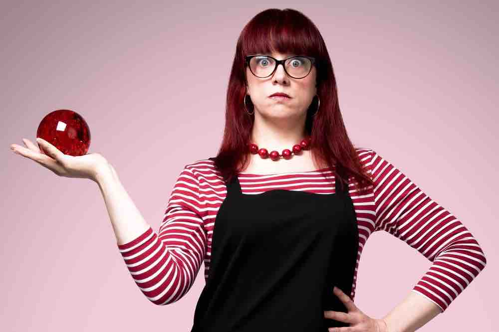 Comedian Angela Barnes red hair holding red glass ball pinafore and red striped t-shirt