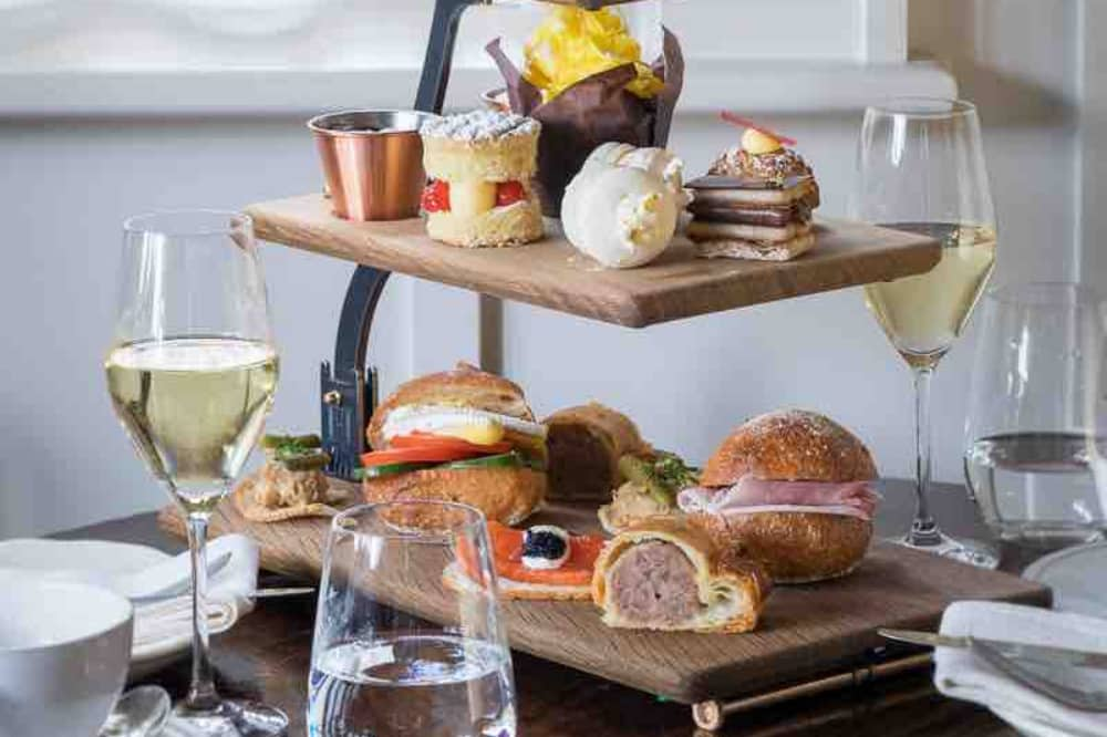 Hurley House Hotel afternoon tea rolls cakes scones and sausage rolls on wooden boards