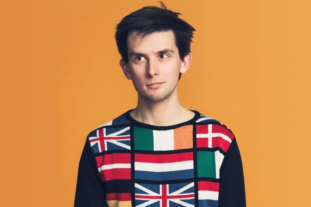 Kieran Hodges '75 comedian orca background flag jumper and mesy brown hair