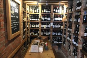 Old Butcher's Wine Cellar with low pine table and walls of wine cookham Berkshire