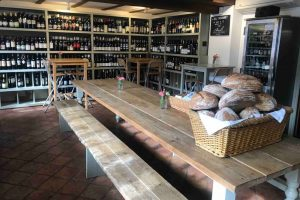 Old butchers wine cellar and pop up bar Cookham Berkshire walls of wine and large wooden table and benches in the middle