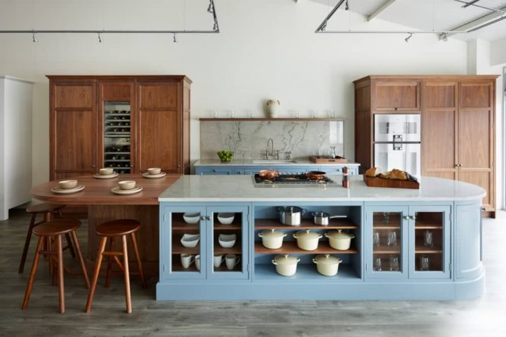 Snug Kitchens traditional kitchen design wooden high cupboards blue island cream pots and pans