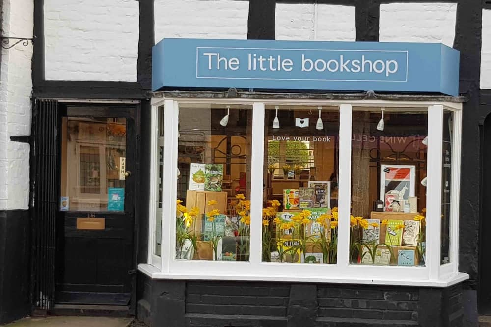 The Little Bookshop Cookham Berkshire white and black tudor building with blue and white sign spring window display