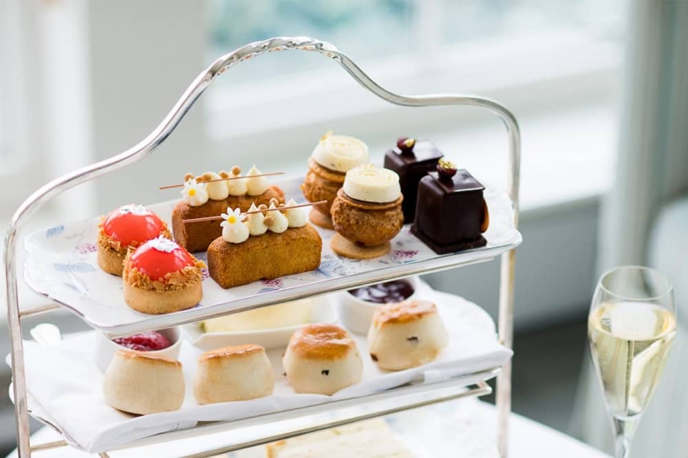 Afternoon tea Berkshire Coworth Park silver cake stand cakes and scones glass champagne