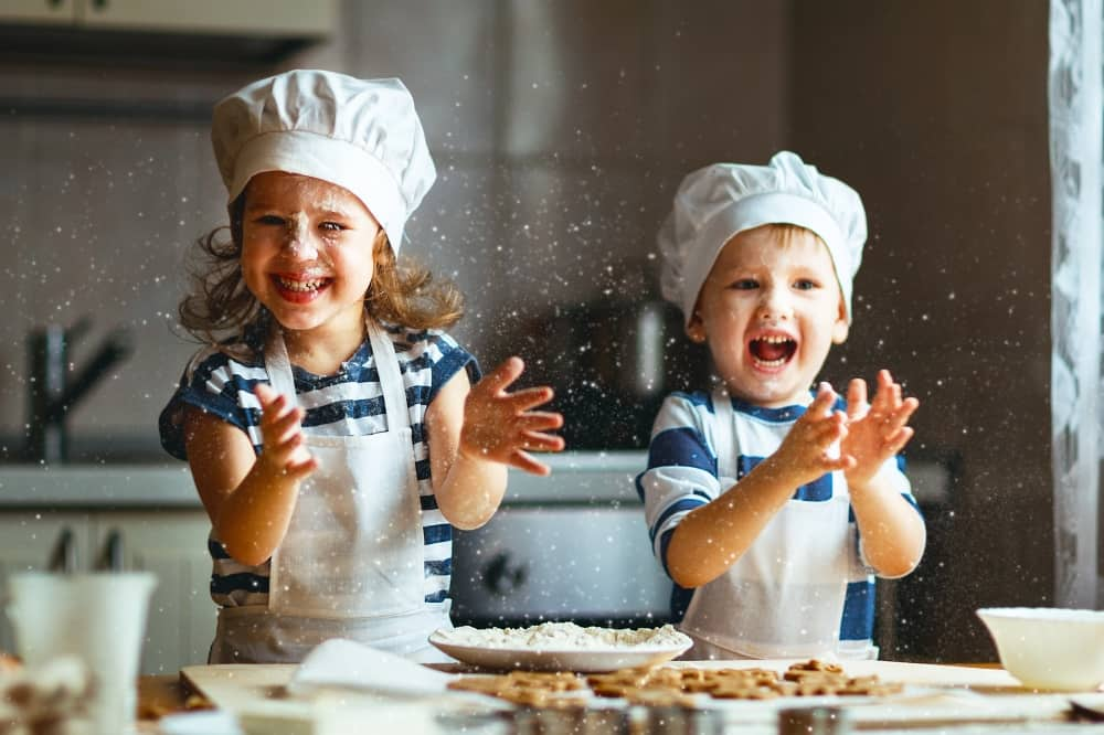 Children boy and girl baking in chefs hats