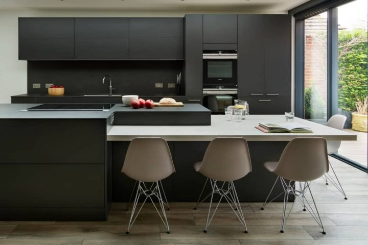Minimal clean lines Snug Kitchens Newbury Berkshire black units marble top and blush pink plastic chairs