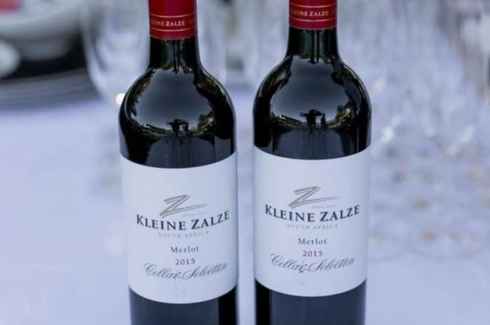 Two bottles of Zalze Lodge Merlot ono whote table cloth empty glasses