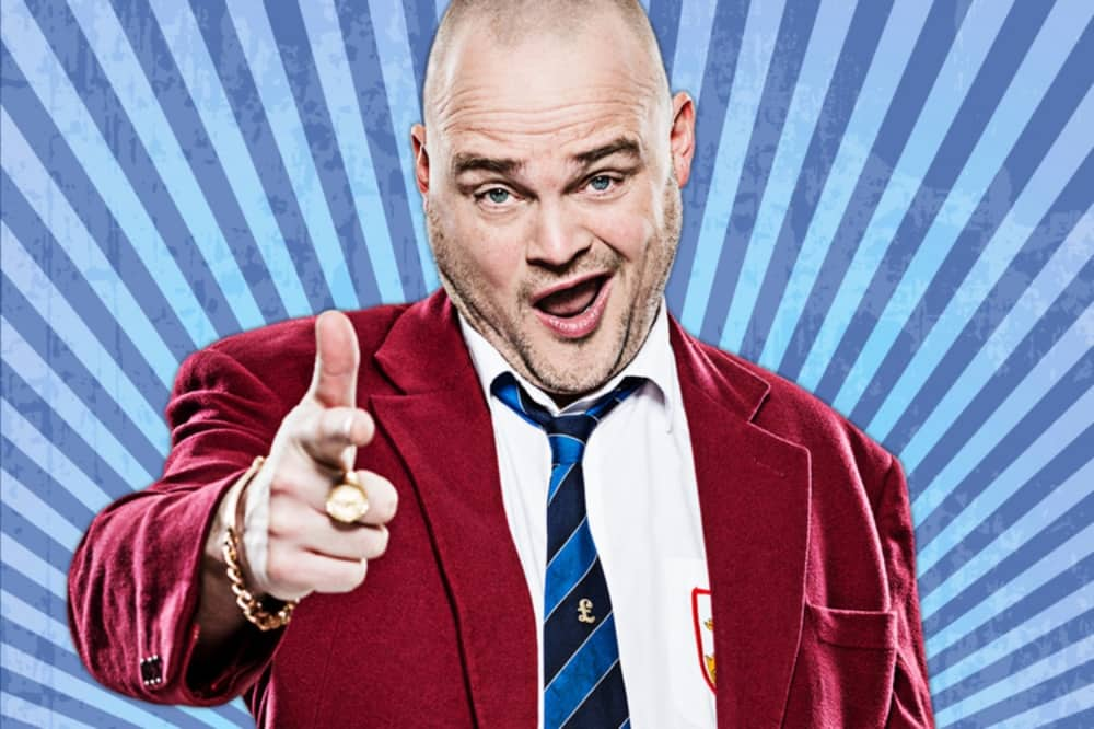 Al Murray pub landlord comedian burgundy blazer shirt stripy tie bald head