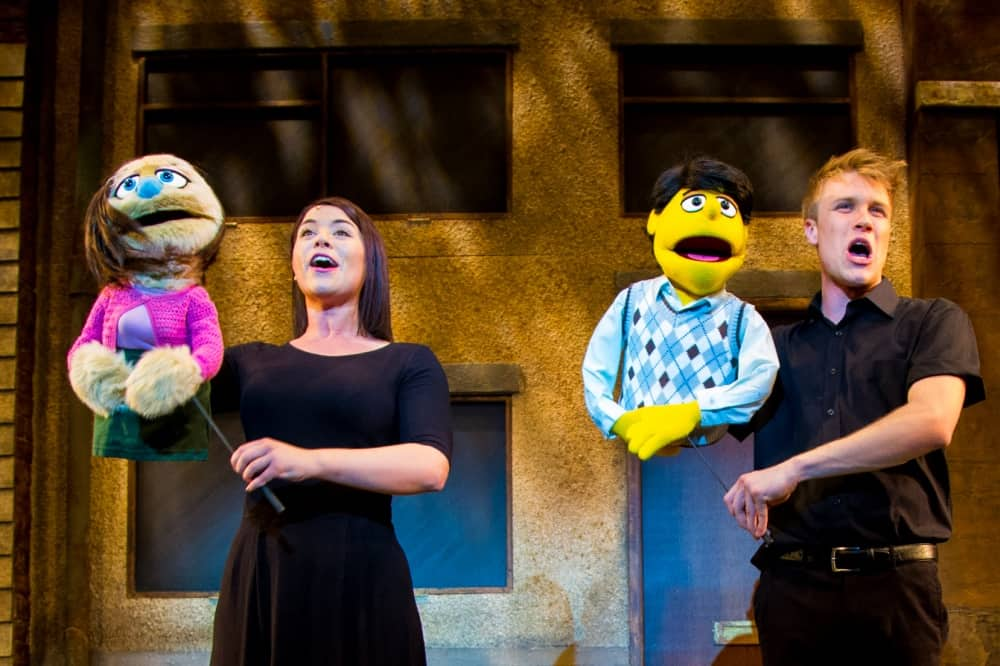 Avenue Q two actor in black with female puppet and male puppet in sweater vest