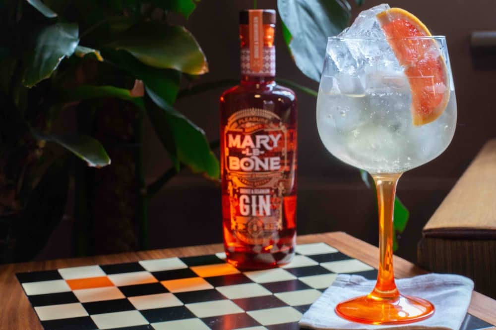 Marylebone Gin new ornage and geranium flavoured gin ornage bottle chess board aand gin balloon glass with orange stem