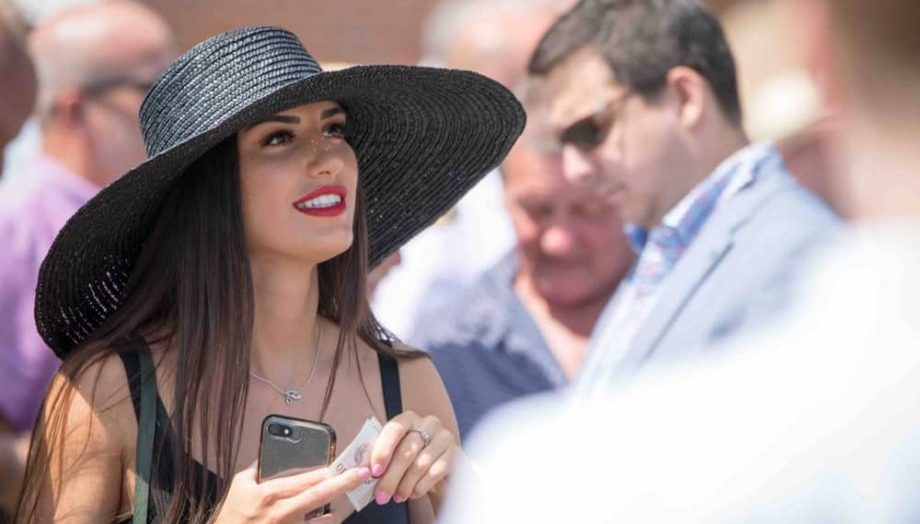 woman in black straw hat at Newbury Races on race day