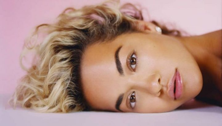 Singer Rita Ora lying down looking at camera