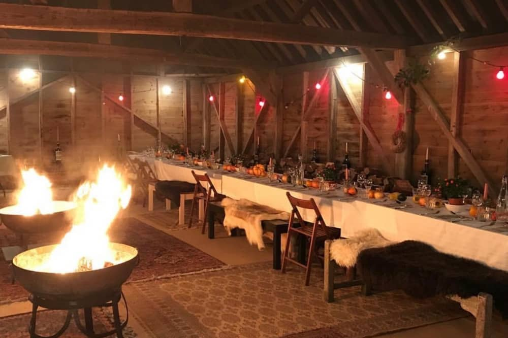 Sadgrove Supper Club barn with exposed beams long tables sheepskins and fairy lights