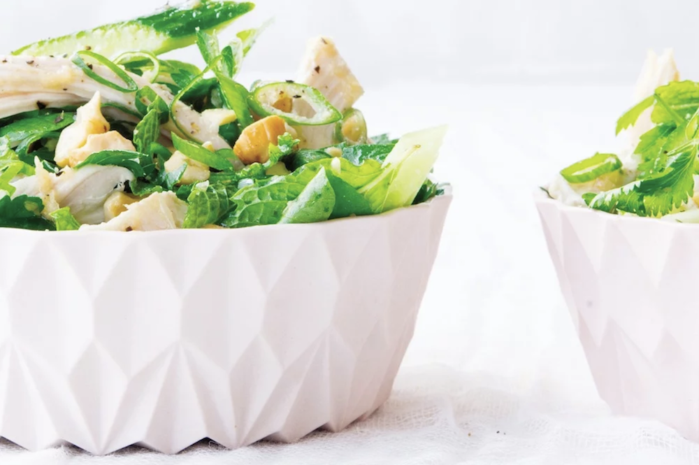 White geometric bowl full of green salad chicken and croutons