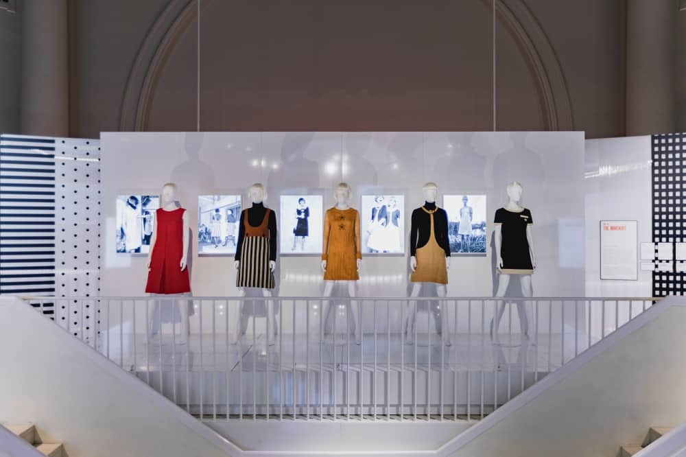 Mary quant exhibition V&A Mary Quant clothes on white mannequins in front of black and white 1960s images