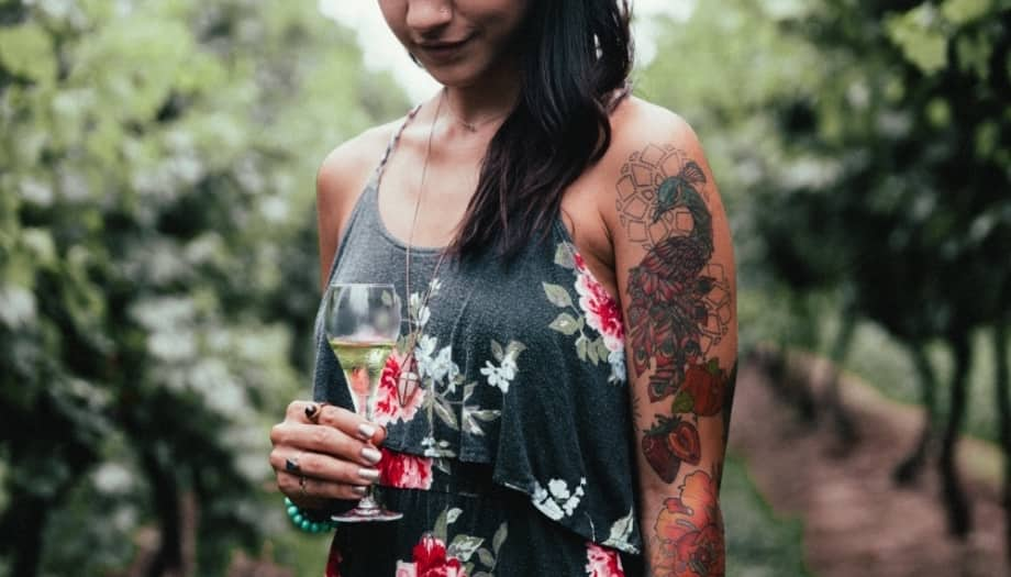 Woman arm tattoos floral dress glass of champagne viineyard