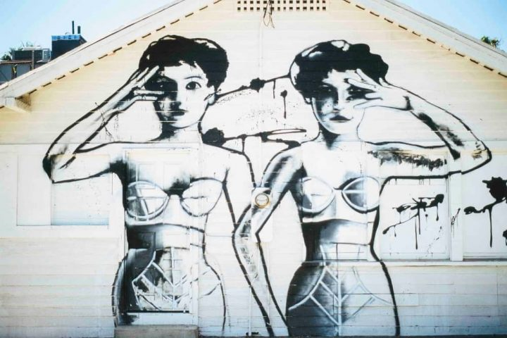 Grafitti on side of house with two women