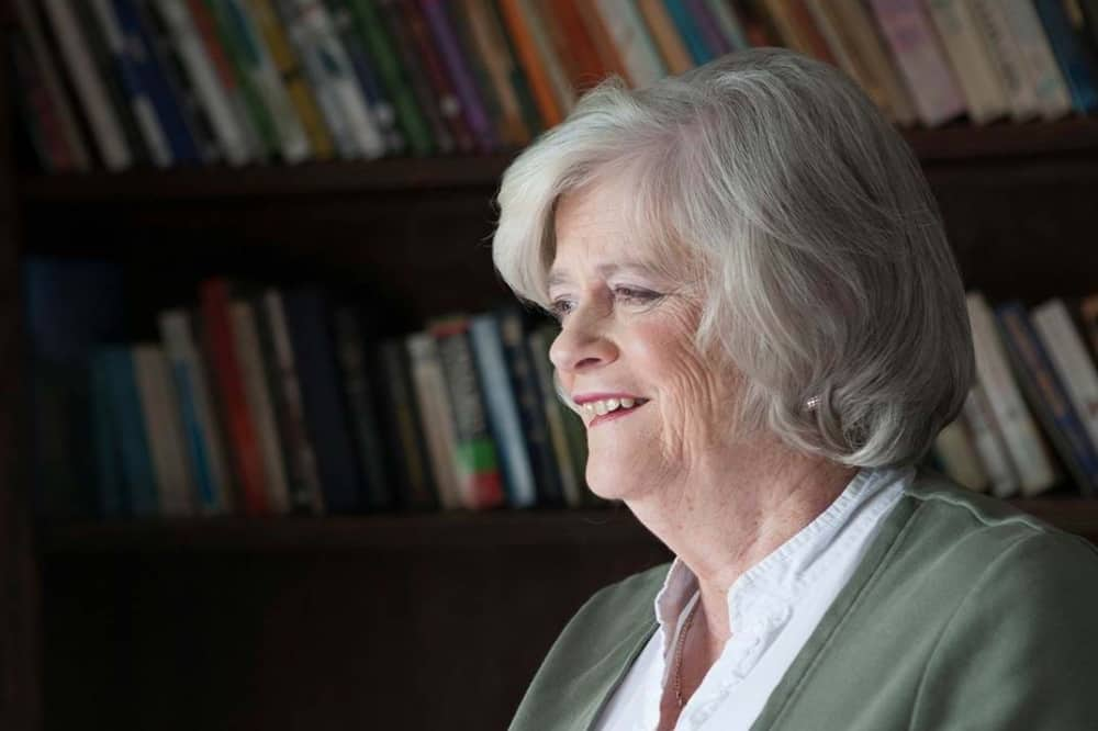 Politician Anne Widdecombe grey short hair surrounded by books on shelf