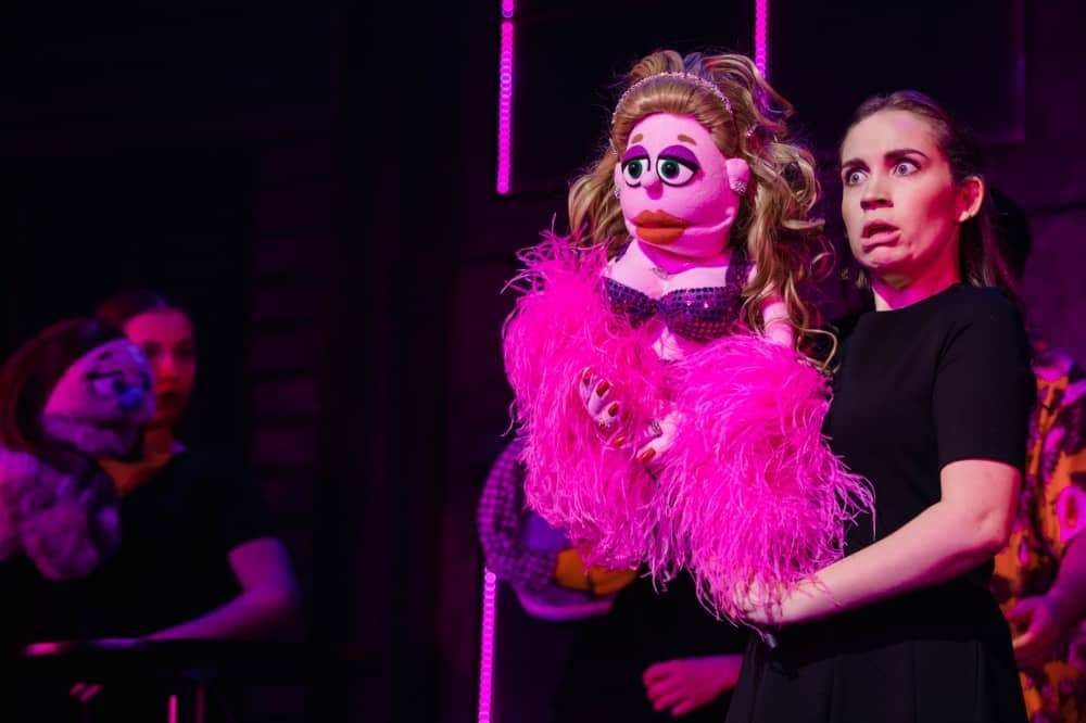 Avenue Q musical Lucy The Slut puppet in pink boa with handler