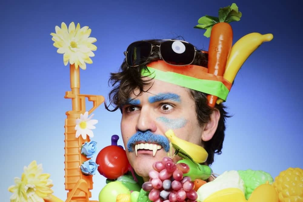 John Luke comedian in green and ornage headband surrounded by fruit