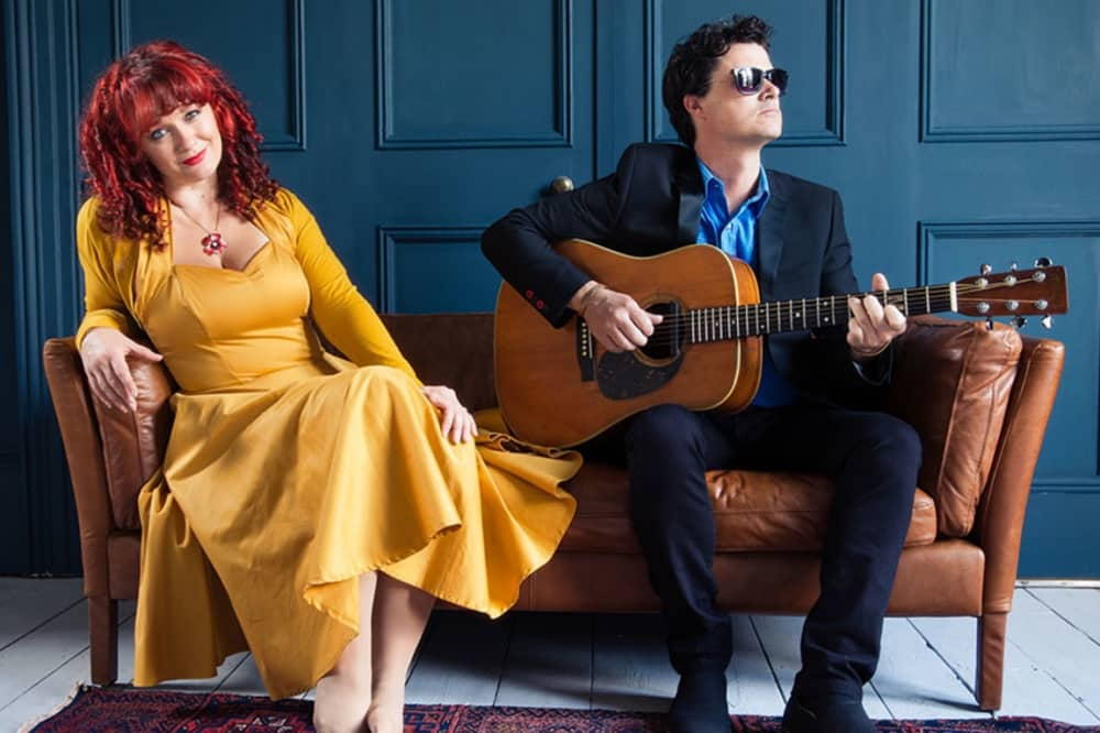 Kathyrn Roberts and Sean Lakeman folk group woman red hair yellow dress with man in blue shhirt and suit with guitar in dark blue panelled room