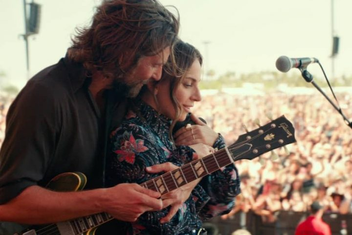Bradley Cooper and Lady Gaga star in A Star Is Born embracing on stage with guitar