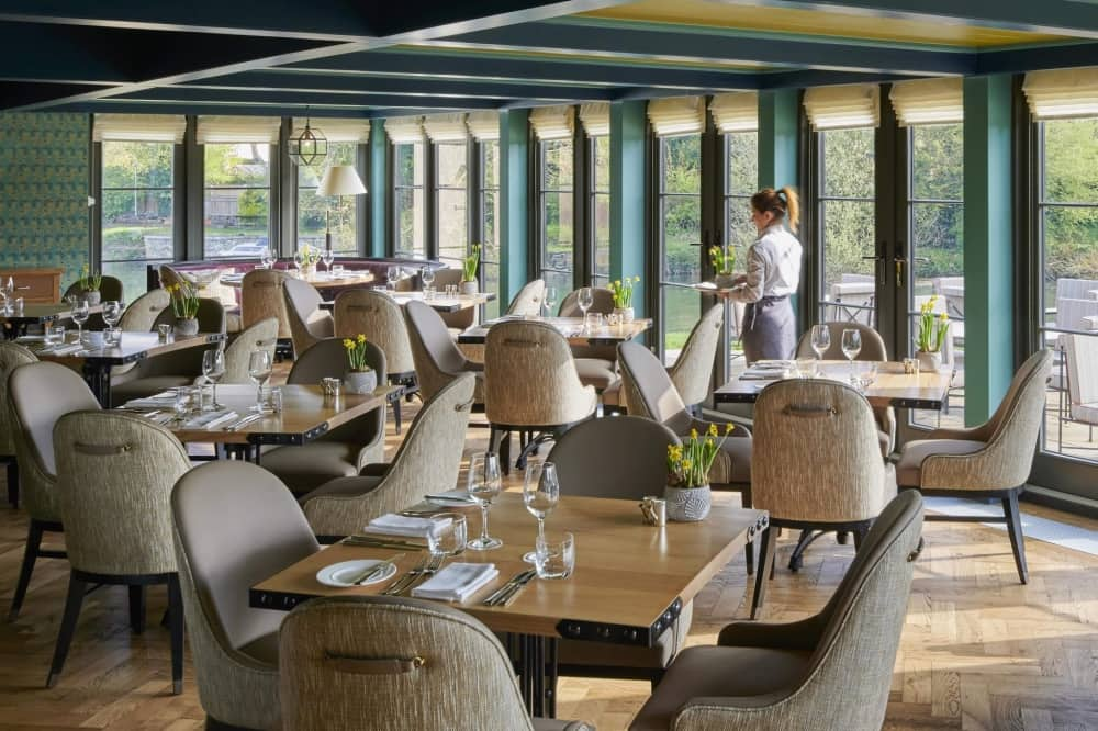 Monkey Island Estate Brasserie yellow and blue ceiling wooden floor open kitchen and upholstered chairs and wooden tables Bray Berkshire