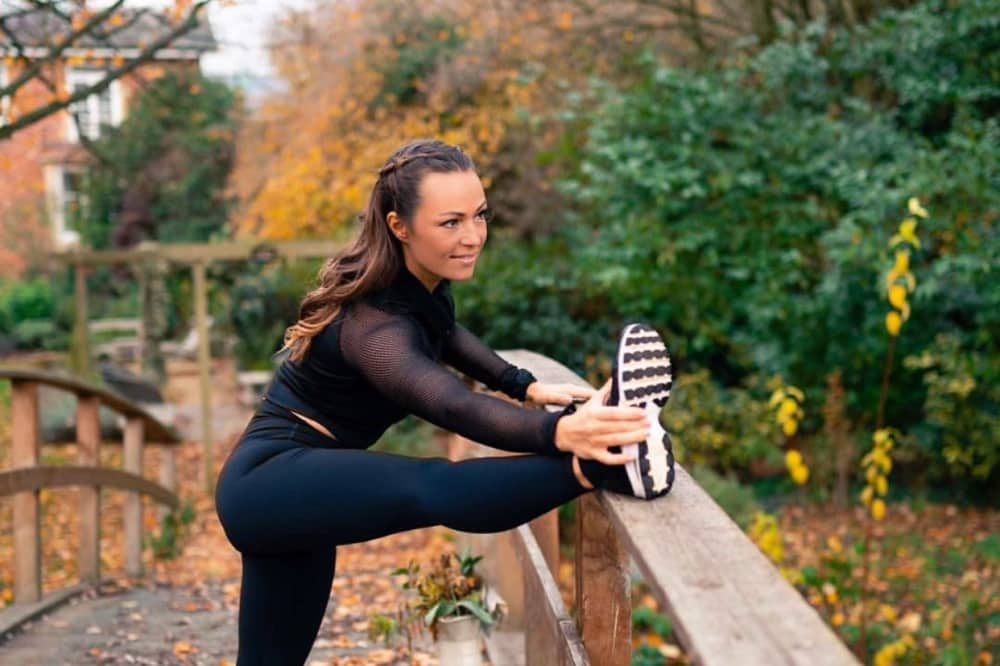 My Fit Zone Anna Cousins stretching on bridge in black leggings and top