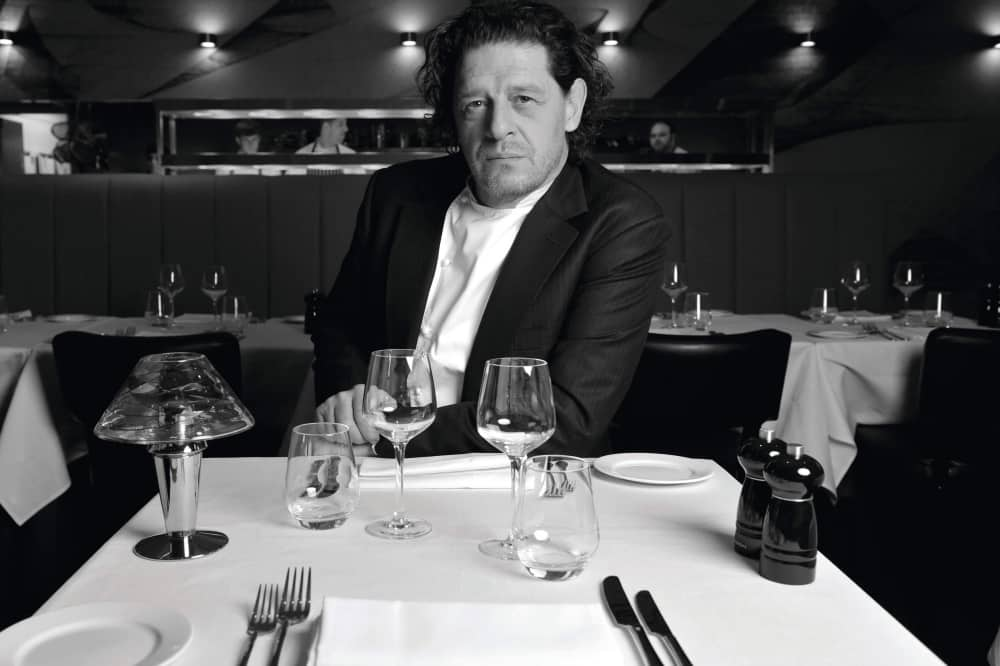 Ihef Marco Pierre White sat at a table in a suit