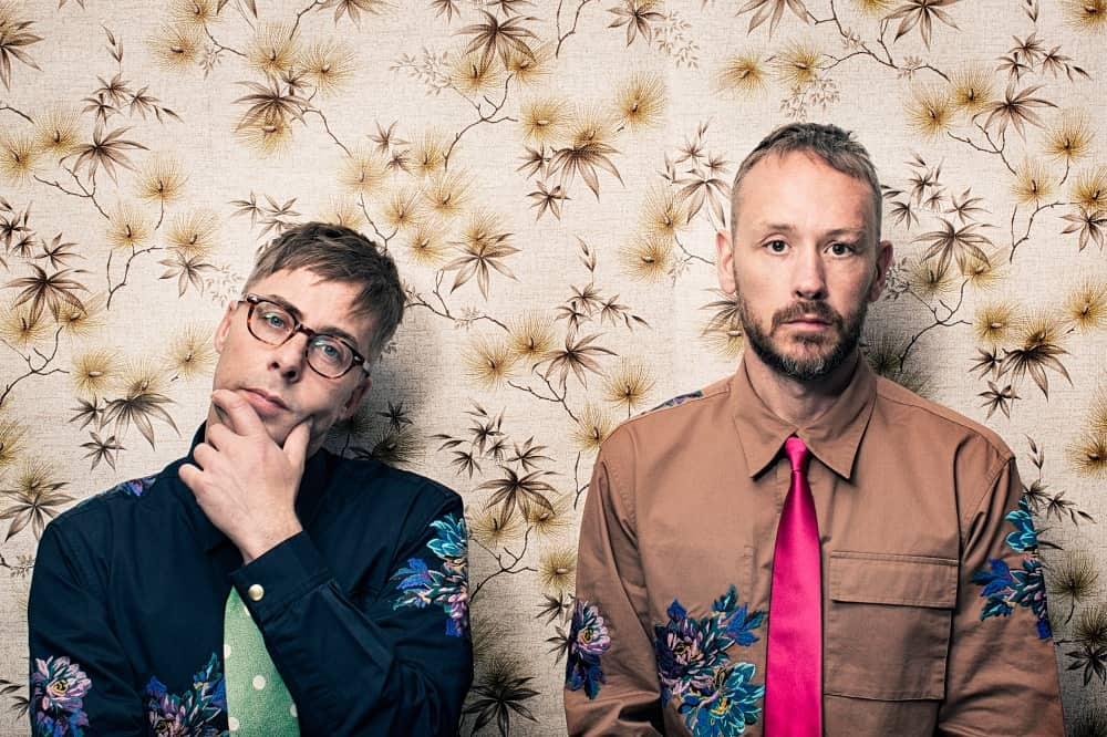 Basement Jaxx stood against floral wallpaper wall