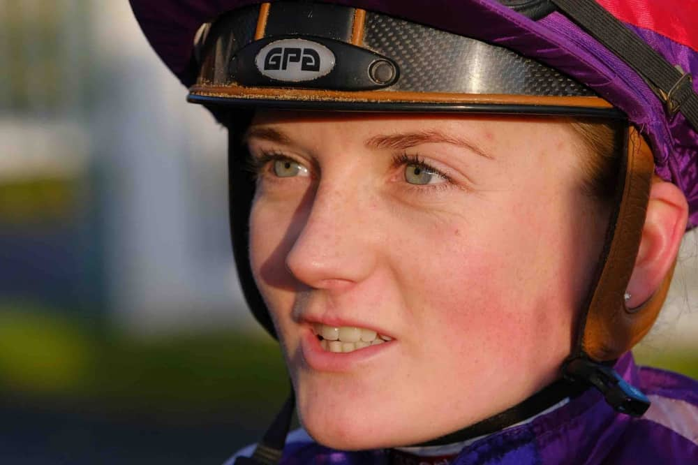 Female flat racing jockey Hollie Doyle in riding hat and purple silk